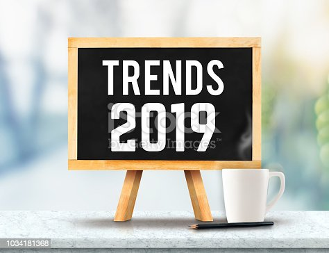 istock Trends 2019 on blackboard with easel on marble table with sun and blur green tree bokeh background.business vision concept. 1034181368