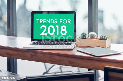istock Trends for 2018 word in laptop computer screen with tablet on wood stood table in at window with blur background,Digital Business or marketing trending 868377350