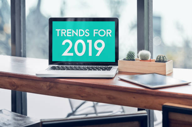 Trends for 2019 word in laptop computer screen with tablet on wood stood table in at window with blur background,Digital Business or marketing trending. stock photo