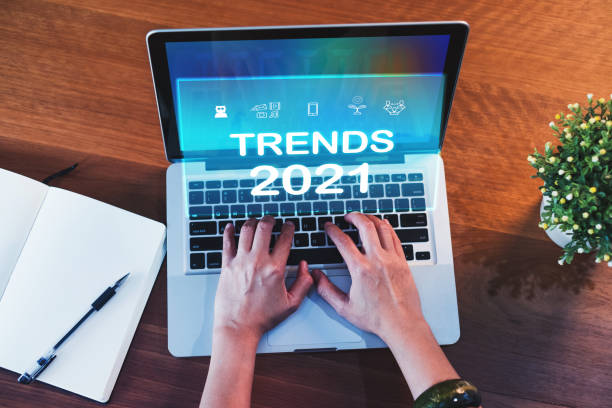 Trends for 2021 augmented reality (AR) floating screen with hand typing keyboard on laptop and notebook on wood table,Digital Business disruption or marketing trending.digital transformation stock photo
