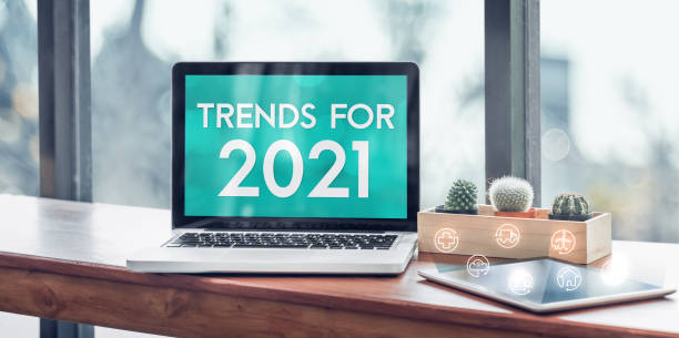 Trends for 2021 in laptop computer screen with icon floating on tablet on wood stood table in at window with blur background,Digital Business or marketing trending stock photo