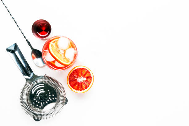 Trendy alcoholic cocktail Negroni with dry gin, red vermouth and red bitter, orange slice and ice cubes. White background, bar tools, top view, copy space Trendy alcoholic cocktail Negroni with dry gin, red vermouth and red bitter, orange slice and ice cubes. White background, bar tools, top view, copy space cocktail shaker stock pictures, royalty-free photos & images