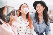 Trendy asian girls making video story for social network app outdoor - Young women friends having fun making live feed - New technology trends and friendship concept - Focus on person blowing