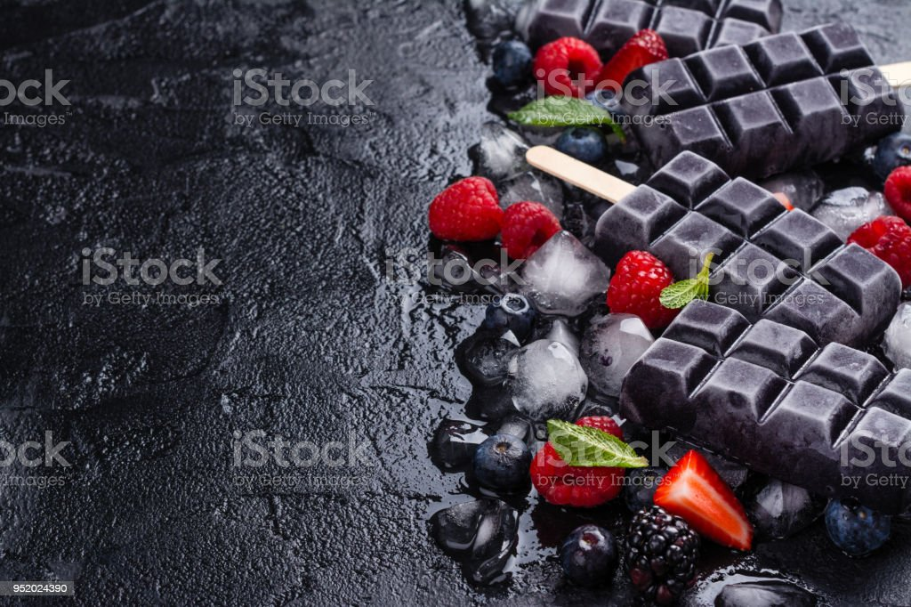 Trendy black charcoal ice cream popsicles stock photo