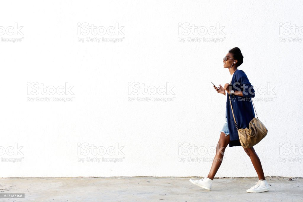 Trendy black woman listening music on mobile phone stock photo