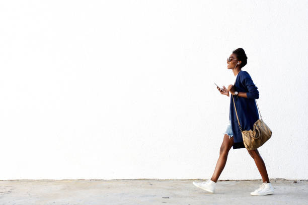 trendy black woman listening music on mobile phone - walking zdjęcia i obrazy z banku zdjęć