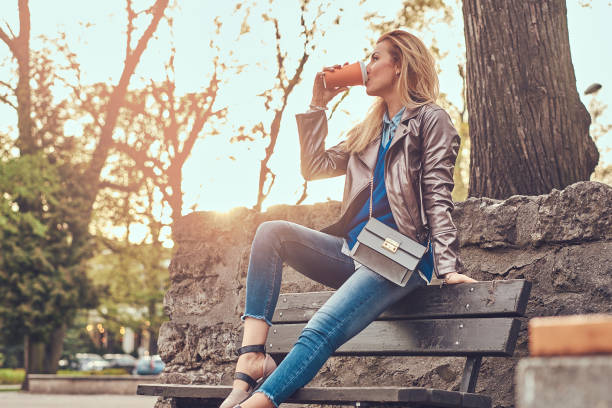 trendige blonde frau entspannt im freien, trinken kaffee zum mitnehmen beim sitzen auf der bank im stadtpark. - handtasche jeans stock-fotos und bilder