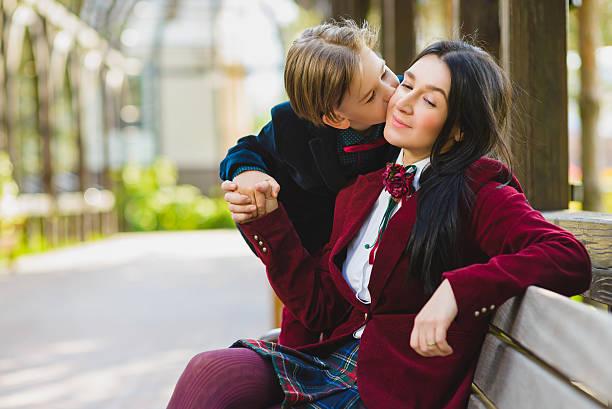 trendige junge küssen seine stilvolle mutter im freien - niedlichen anime jungs stock-fotos und bilder