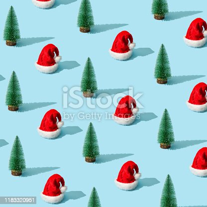 873264516 istock photo Trendy Christmas pattern made with Christmas tree and Santa Claus hat on bright light blue background. 1183320951