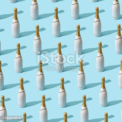 873264516 istock photo Trendy Christmas pattern made with white champagne bottle on bright light blue background. 1183320979