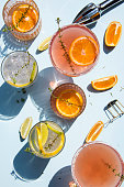 Trendy cocktails on light blue background with lemon and orange slices. Abstract conception.