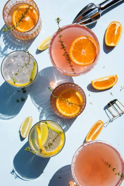 Trendy cocktails on light blue background with lemon and orange slices. Trendy cocktails on light blue background with lemon and orange slices. Abstract conception. still life stock pictures, royalty-free photos & images