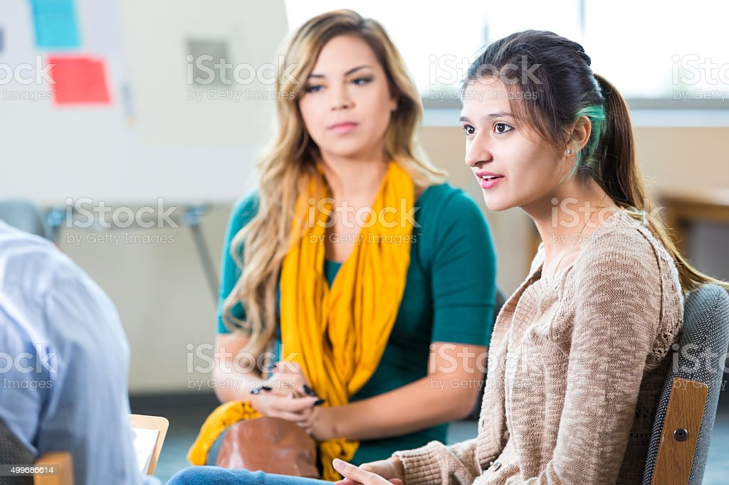 Trendy college age women discussing something in class or therapy stock photo