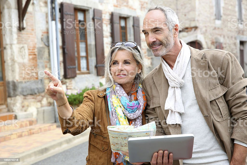 Trendy couple using tablet during visit of town stock photo