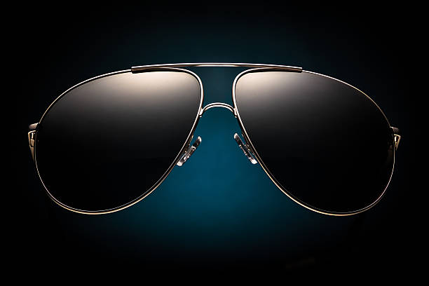 Trendy dark sunglasses on a black background with blue spot stock photo