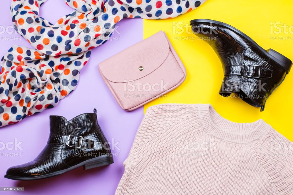 Trendy female autumn clothing. Stylish ankle boots, pink sweater, pink purse and printed scarf on a bright background stock photo