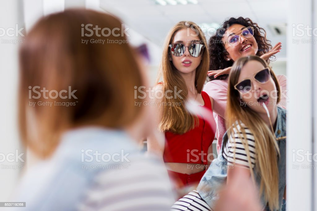 Trendy female friends trying on stylish sunglasses looking in mirror, smiling, having fun in accessory store stock photo