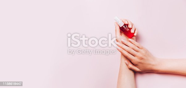 946930880istockphoto Trendy female manicure. Woman's hands holding nail treatment on pink background. 1158618447