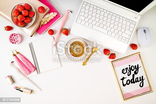 Trendy feminine home workplace. Home office desk with laptop, notebook, fresh strawberries, cosmetics, accessories and coffee cup on white background. Flat lay, top view