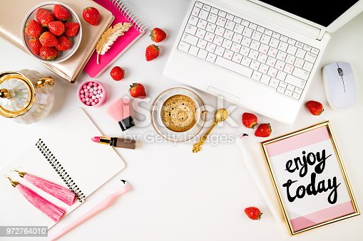509867718istockphoto Trendy feminine home workplace. Home office desk with laptop, notebook, fresh strawberries, cosmetics, accessories and coffee cup on white background. Flat lay 972764010