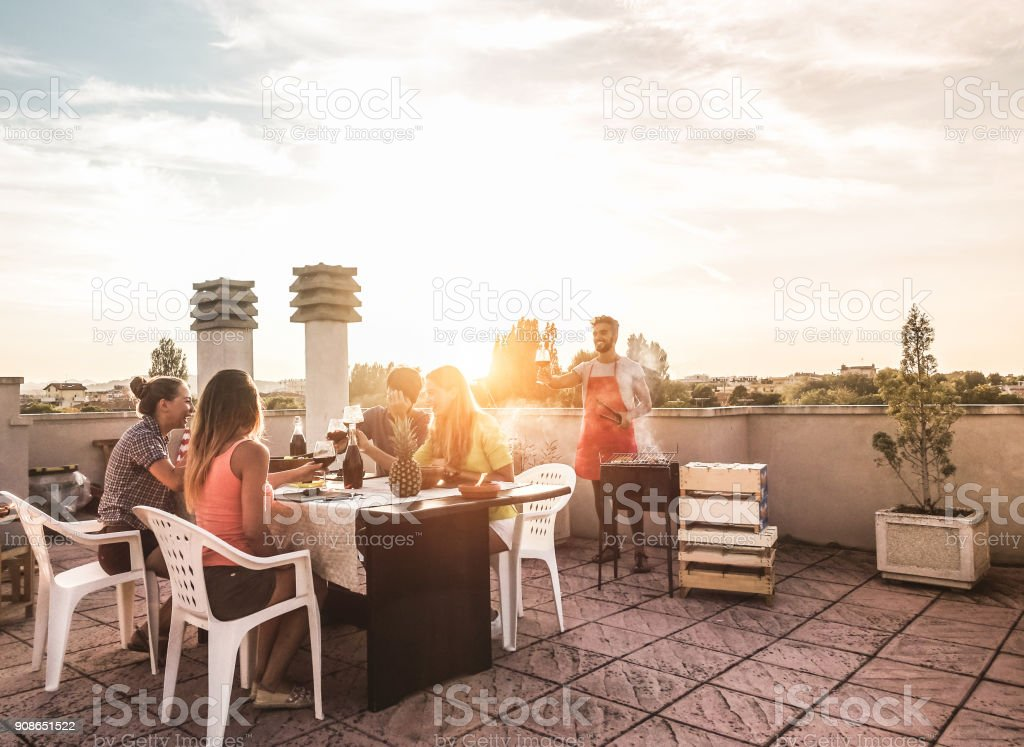 Trendy friends having barbecue party on top of the roof - Happy people doing bbq dinner outdoor - Main focus on woman with yellow t-shirt - Fun, summer, city lifestyle and friendship concept stock photo