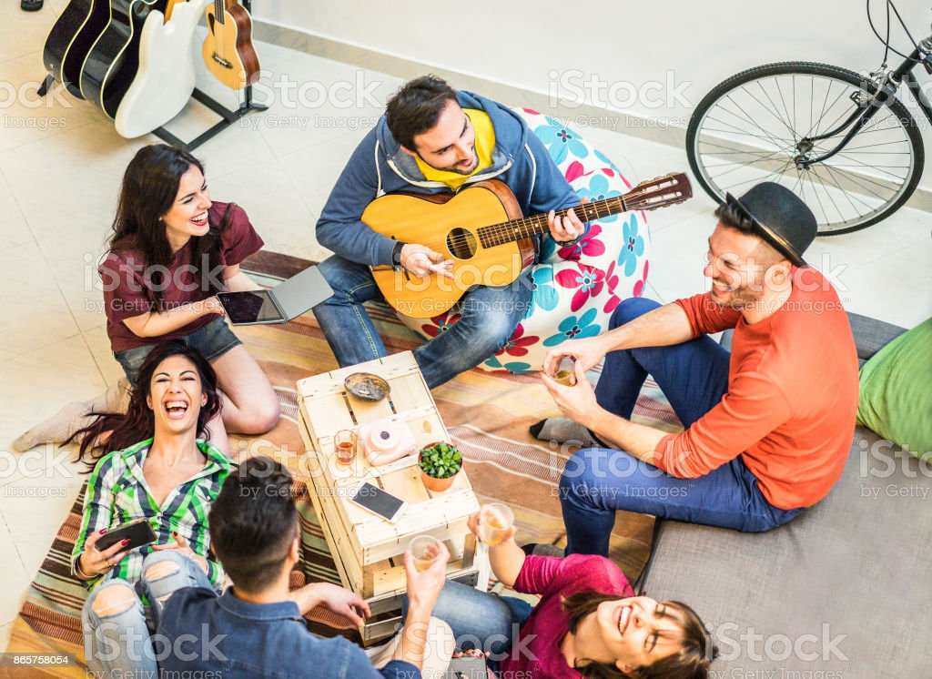 Trendy friends having fun in home living room - Happy young people enjoying time together playing music and drinking shots - Friendship and youth concept - Main focus on top left guys - Warm filter stock photo