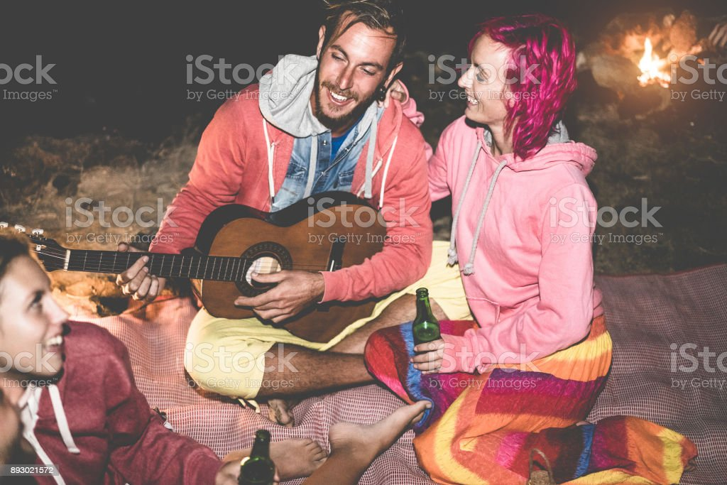 Trendy friends playing guitar and drinking beer next bonfire outdoor - Happy people having fun camping in vacation holidays - Focus on man face - Friendship, party and nature concept - Contrast filter stock photo