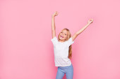 Trendy funtime leisure rest relax lifestyle concept. Portrait of cute lovely sweet adorable cheerful excited tender gentle joyful delightful carefree girl raising hands up isolated on pink background