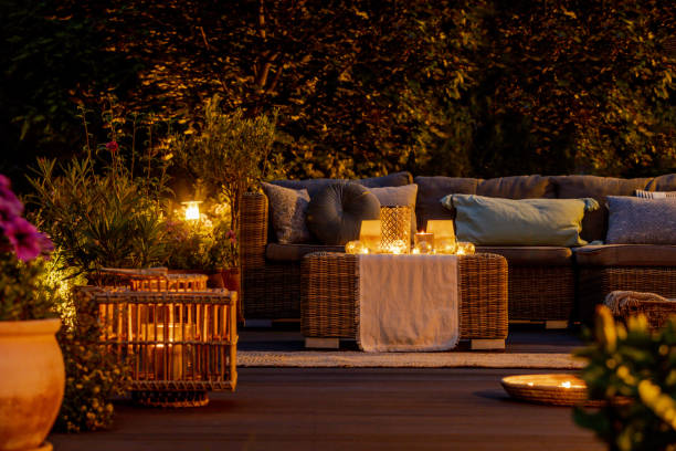Trendy furniture, lights, lanterns and candles in the garden at night stock photo