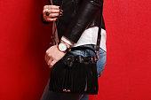 Trendy girl in jeans holding black fringe bag