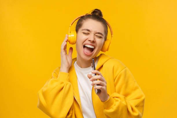 時髦的女孩在電話裡大聲唱著最喜歡的歌作為麥克風, 戴著無線耳機, 孤立的黃色背景。卡拉ok在線應用程式。 - 少女 個照片及圖片檔