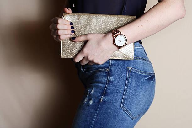 trendige mädchen mit gold-clutch und erleben sie schönheit, mode-konzept. - handtasche jeans stock-fotos und bilder