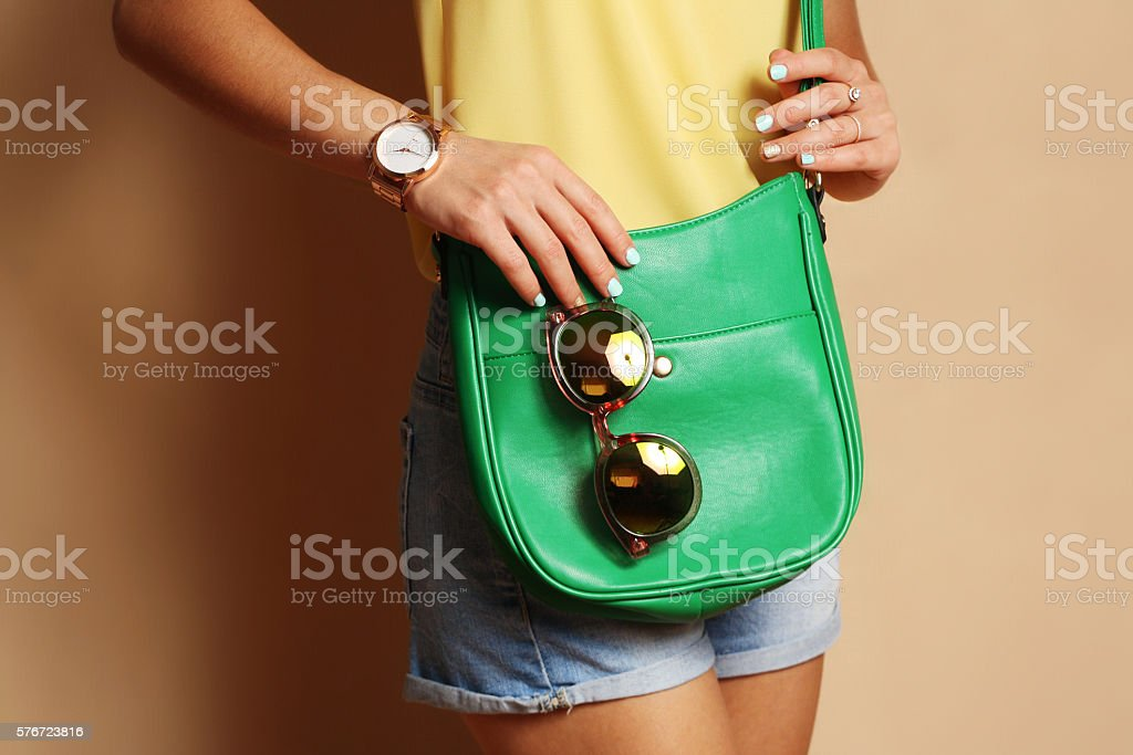 Trendy girl with green handbag clutch and sunglasses stock photo