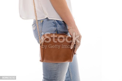 509923232 istock photo Trendy girl with small brown leather bag handbag in hand 509923232