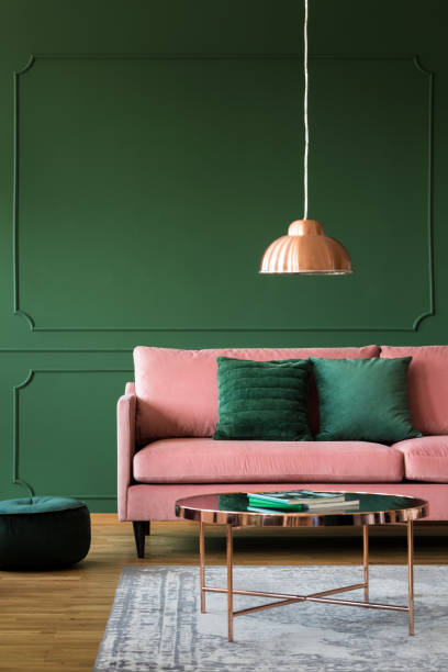 Trendy green living room with pink velvet sofa