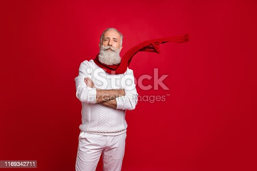 istock Trendy grey-haired superhero fearless santa wear warm knitted clothes isolated red background 1169342711