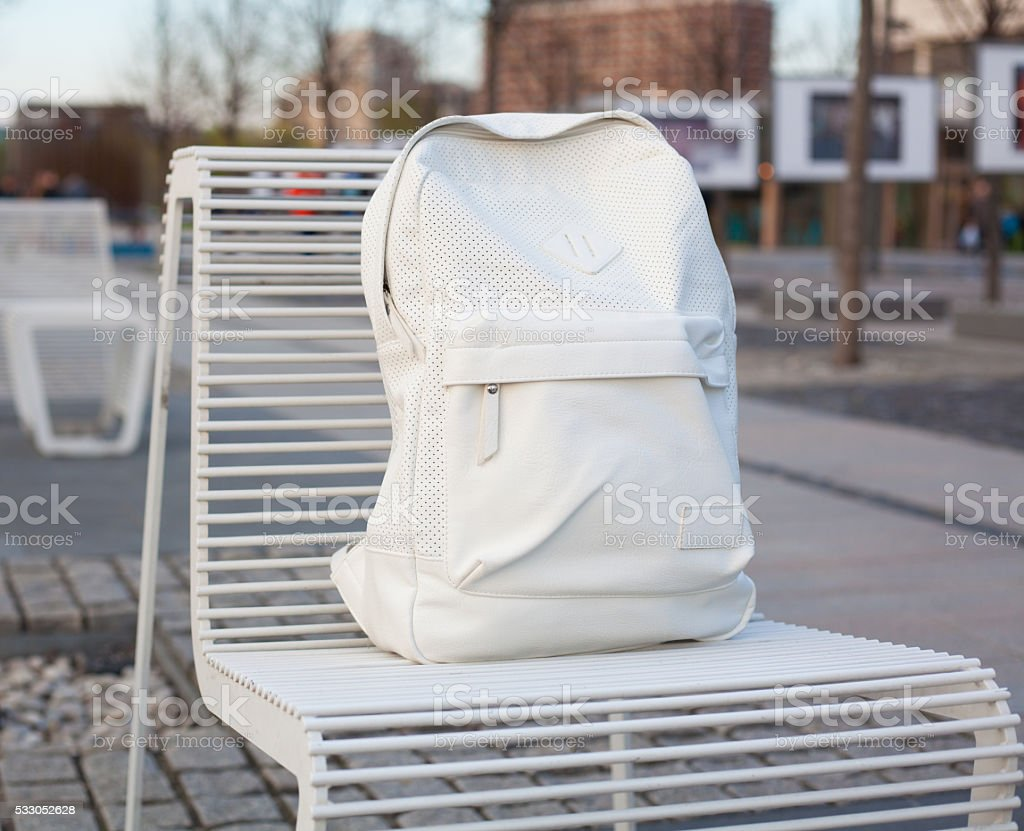 Trendy handsome backpack on a chair in the park.  Object. stock photo