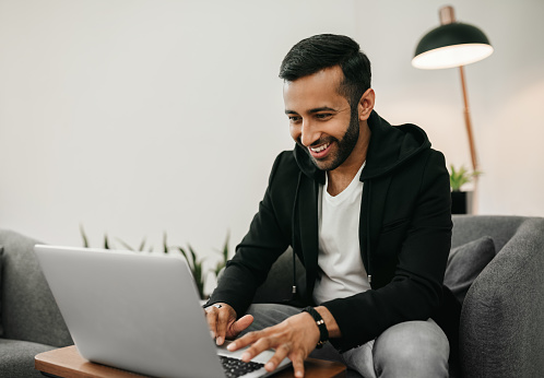 Trendy handsome Gen z Indian arabic man working on laptop in waiting area, Smiling and staring at screen