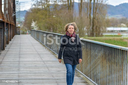 Trendy healthy middle-aged woman walking outdoors on a cold winter day in her jeans, coat and scarf crossing a pedestrian bridge approaching with a happy smile