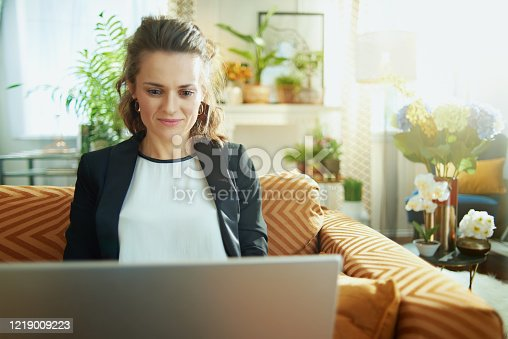 trendy housewife in white blouse and black jacket in the modern house in sunny day writing on a laptop while sitting on sofa.