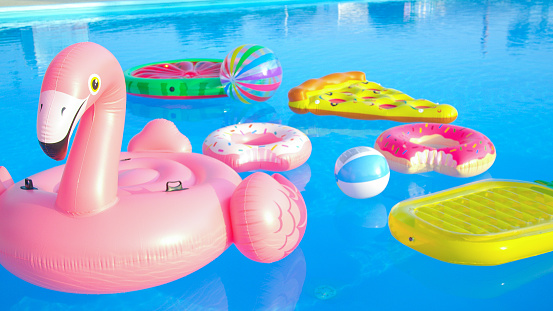 CLOSE UP: Trendy inflatable toys float around the empty pool on a sunny day as all social gatherings are cancelled until further notice due to coronavirus outbreak. Empty pool after a cancelled party.
