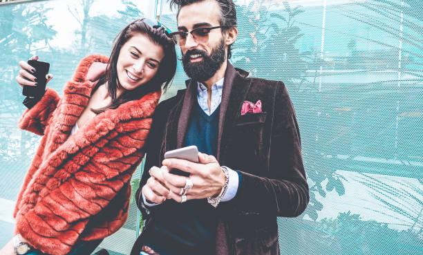 trendiga influentials människor använder smartphone sociala medier app - ungt mode par titta berättelsen video på mobiltelefon - tekniktrender, marknadsföring och nya digitala jobb koncept - fokus på ansikte människan - new job bildbanksfoton och bilder