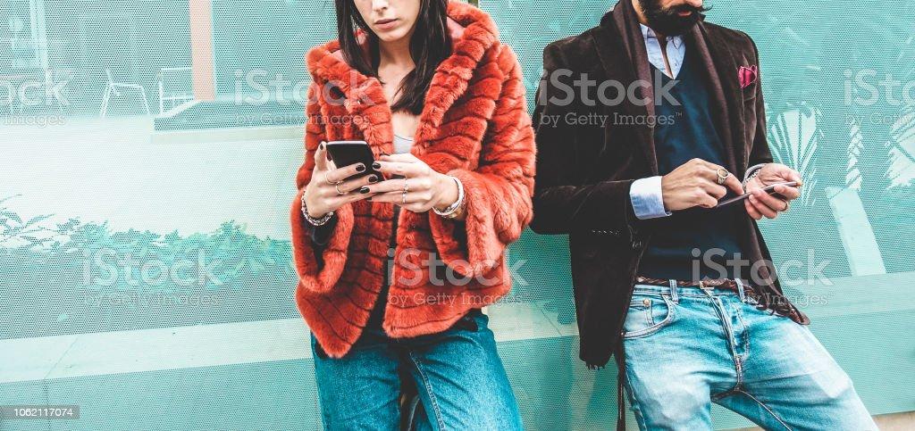 時尚影響者使用智慧手機社交媒體應用程式-年輕的時裝夫婦在手機上觀看故事視頻-技術趨勢, 行銷和新的數位工作概念-專注于手 - 免版稅一起圖庫照片
