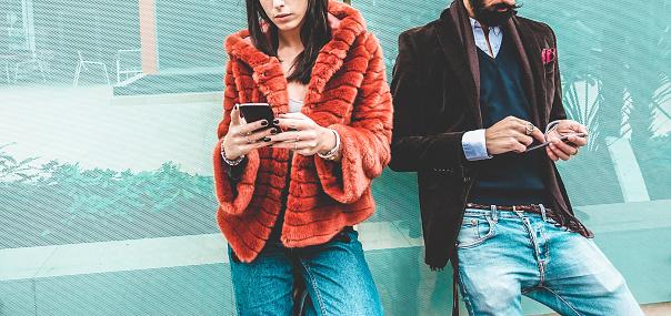 時尚影響者使用智慧手機社交媒體應用程式年輕的時裝夫婦在手機上觀看故事視頻技術趨勢 行銷和新的數位工作概念專注于手 照片檔及更多 一起 照片