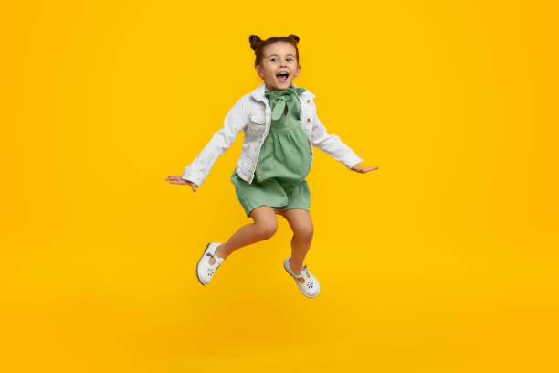 Trendy kid jumping and screaming Adorable little girl in stylish dress and jacket yelling and leaping up in excitement against bright yellow background mid air stock pictures, royalty-free photos & images