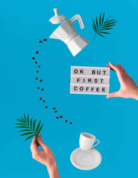 Trendy levitation. Flying line of coffee beans between ceramic coffee maker and espresso cup. Palm leaf and lightboard with text OK but coffee first in hands on blue mint background. stock photo