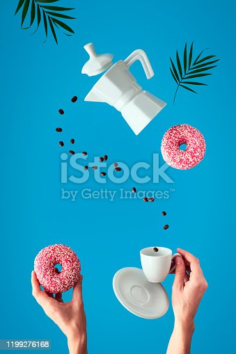 Trendy levitation. Flying line of coffee beans between ceramic coffee maker and espresso cup with saucer. Two female hands hold pink doughnuts with sugar icing. Blue mint background with palm leaves.