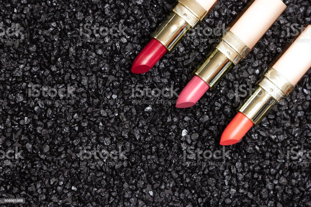 Close-up of lipstick various colors on anthracite surface, copy...
