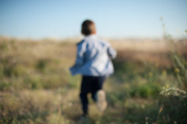 trendy little boy running among the grass in a blurred focus stock photo