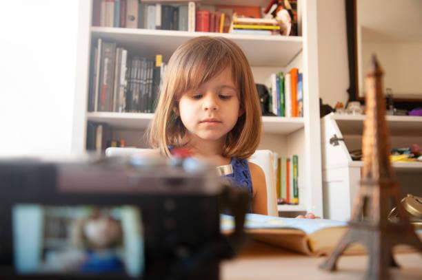 la petite fille à la mode dans l'été vêtements occasionnels et chapeau blanc s'enregistre avec un appareil photo à la maison. sur le bureau il ya un souvenir en métal de la tour eiffel. bibliothèque blanche sur le fond. petit blogueur. - camera sculpture photos et images de collection